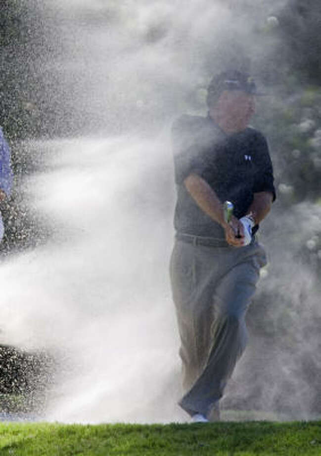 Keith Fergus, former University of Houston golfer, makes a shot out of a bunker on the third hole during the second round. Photo: Johnny Hanson, Chronicle