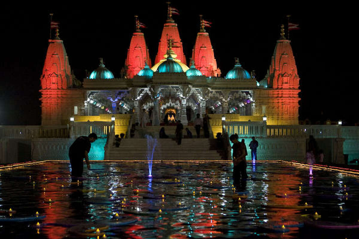 Pragnesh Prajapati (left) and Parul June (right) place battery powered teacup candles on decorations in a reflection pond for the Hindu Diwali festival at the BAPS Swaminaryam Mandir (Temple) Thursday, Oct. 15, 2009, in Stafford.