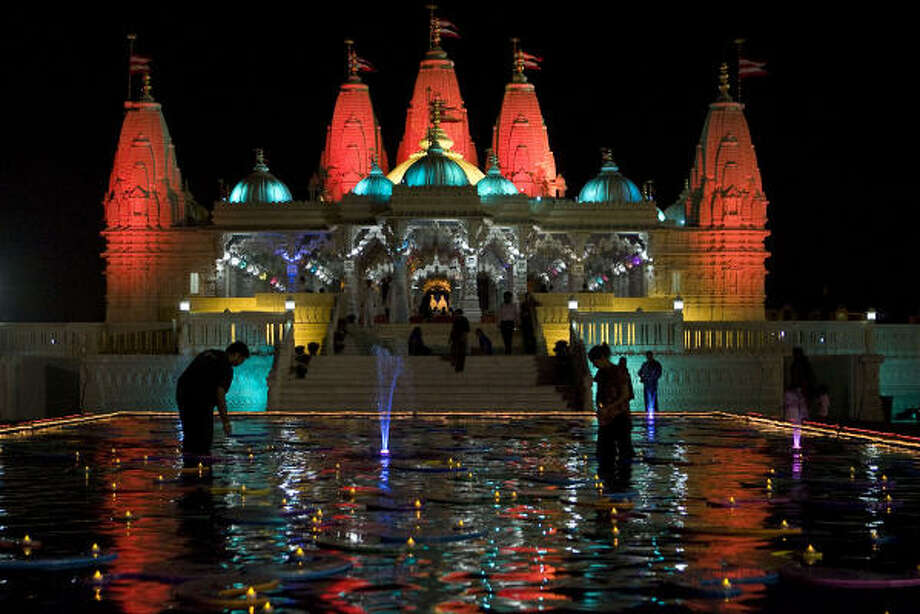 Pragnesh Prajapati (left) and Parul June (right) place battery powered teacup candles on decorations in a reflection pond for the Hindu Diwali festival at the BAPS Swaminaryam Mandir (Temple) Thursday, Oct. 15, 2009, in Stafford. Photo: James Nielsen, Houston Chronicle