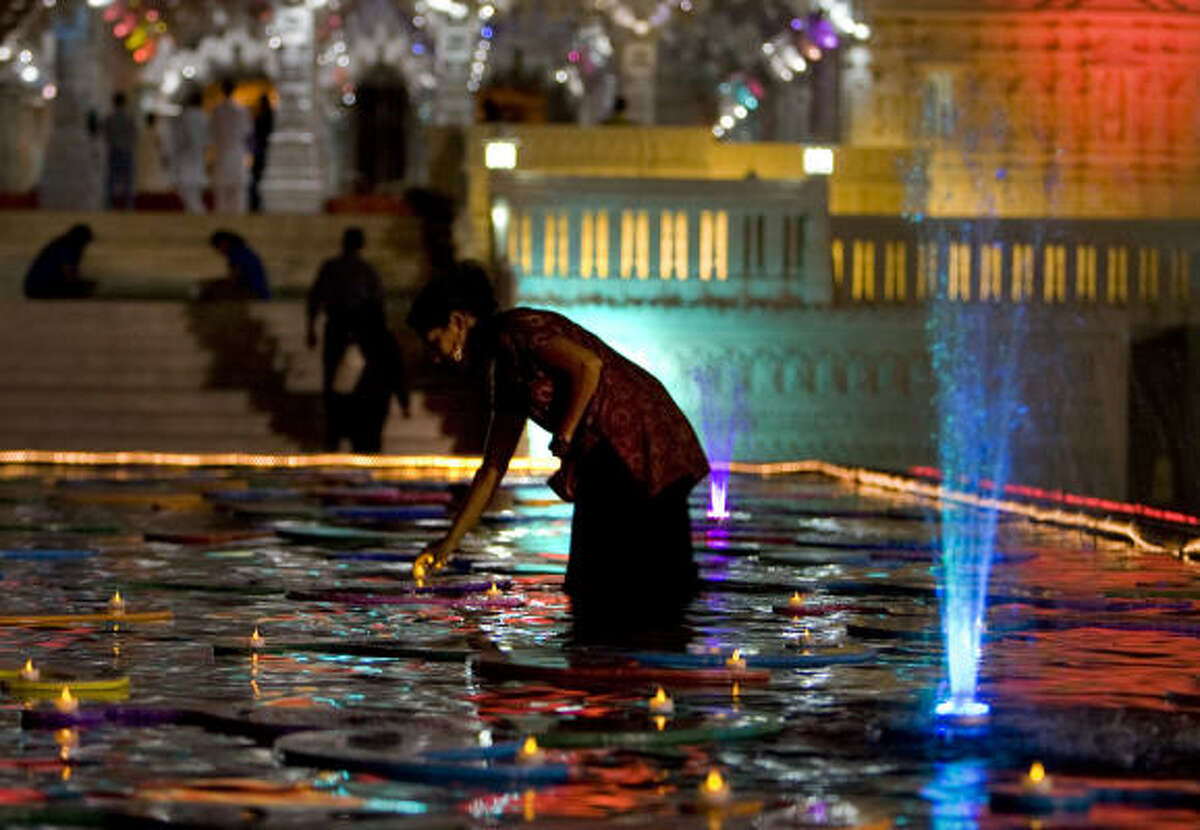 Parul June places battery power teacup candles on floating decorations for the Hindu Diwali festival at the BAPS Swaminaryam Mandir (Temple) Thursday, Oct. 15, 2009, in Stafford.