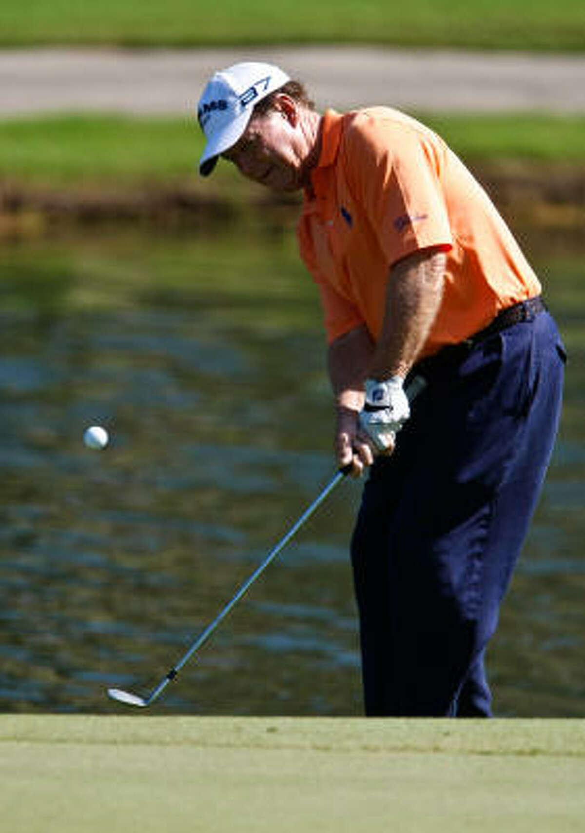 Tom Watson chips a shot onto the green at the third hole.