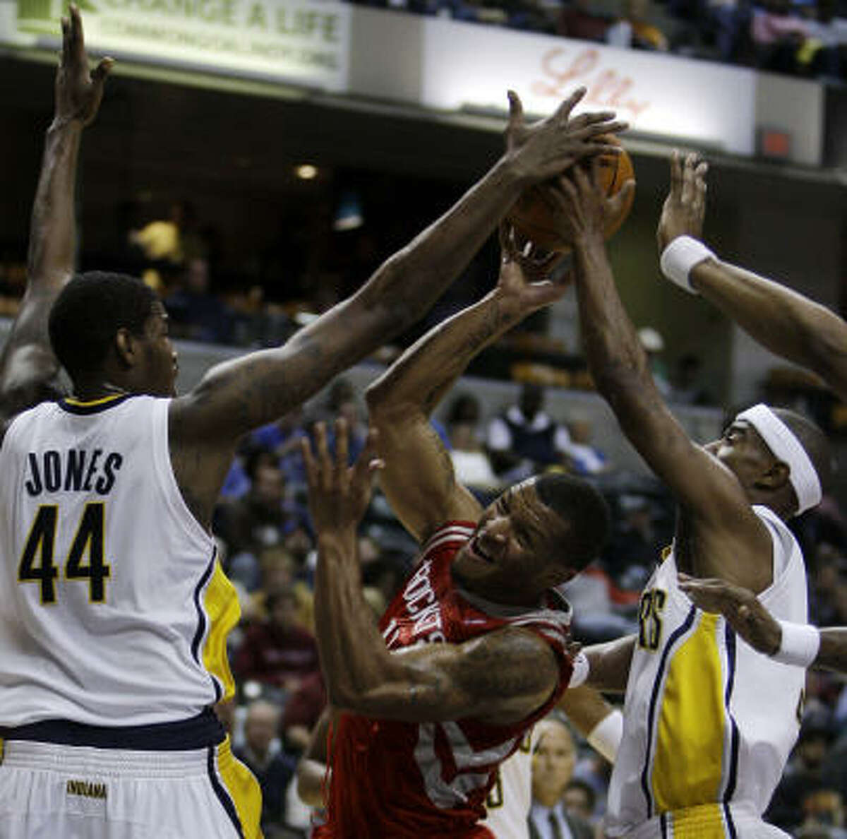 Rockets guard Will Conroy, center, drives to the basket against Pacers center Solomon Jones (44) and guard T.J. Ford during the third quarter.