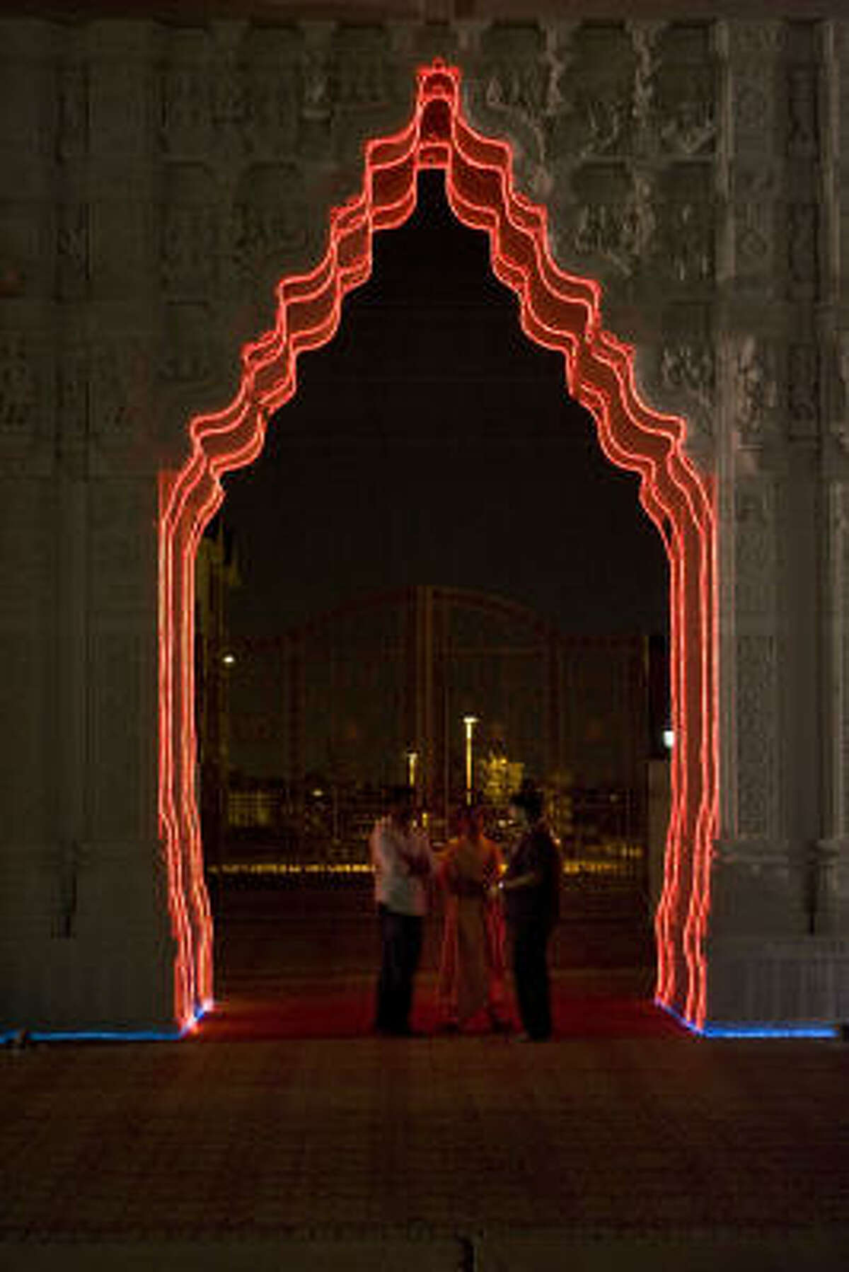 Paresh Patel, from left, Sadhu Shewmunidas and Pragnesh Prajapati stand under an arch during preparations for the festival.