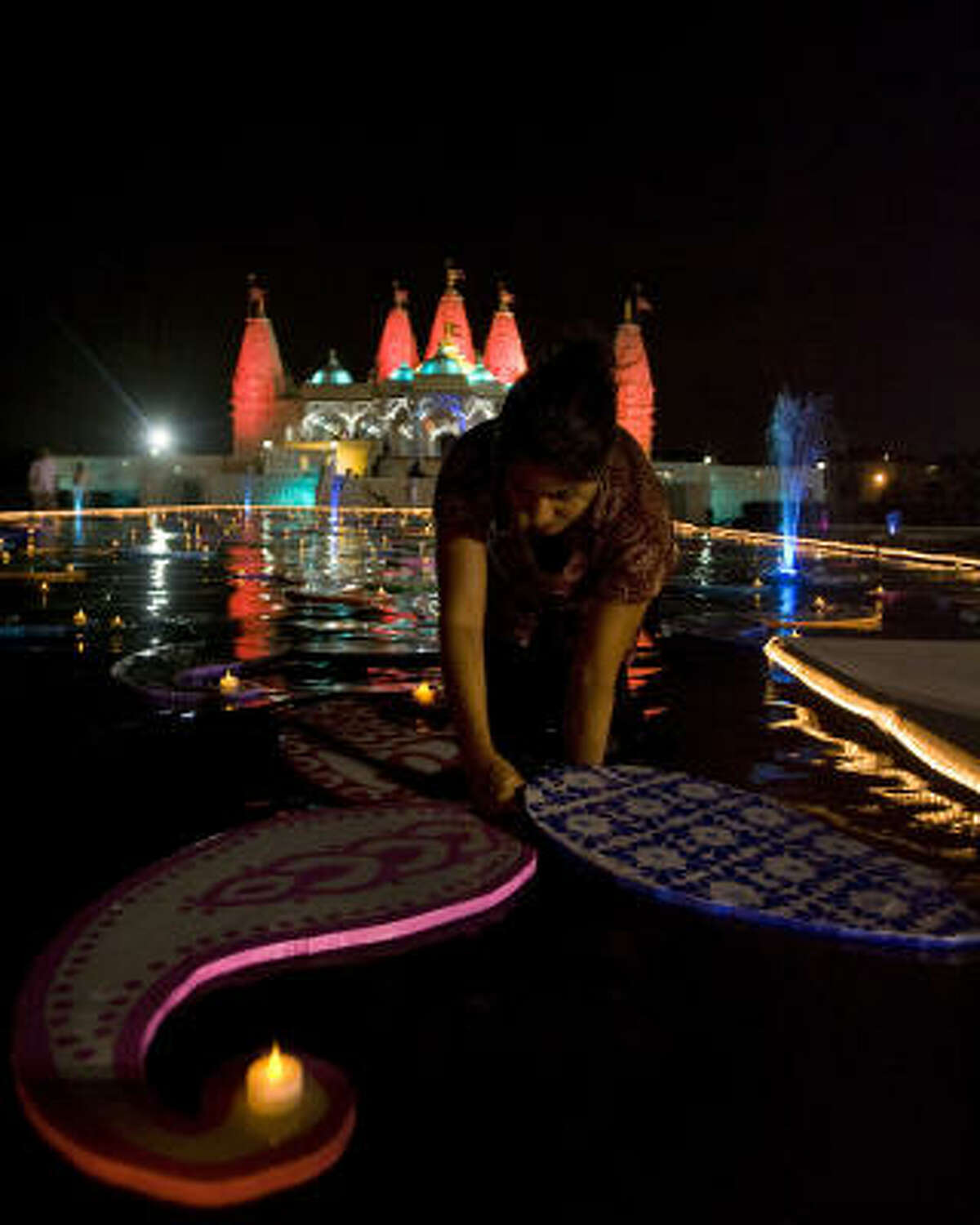 Parul June places battery powered teacup candles on decorations in a reflection pond.