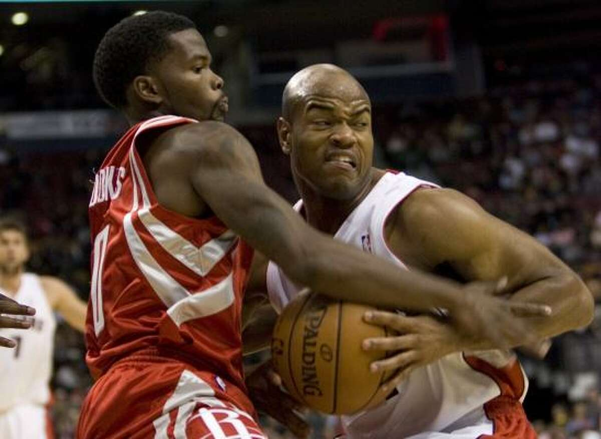Raptors' Jarrett Jack, right, battles Rockets' Aaron Brooks for possession during the first half.