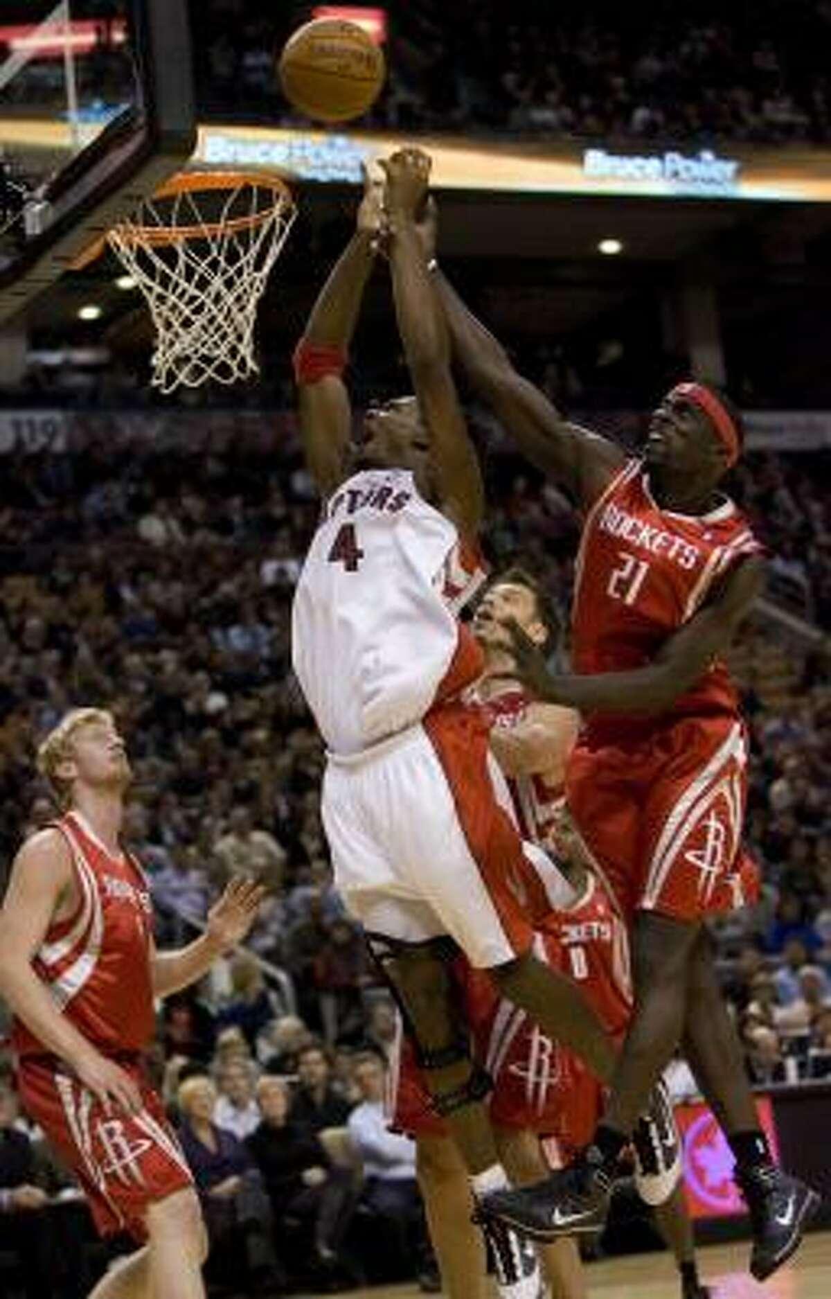 Raptors' Chris Bosh (4) jumps for a rebound with Rockets' Pops Mensah-Bonsu (21) as Rockets' Chase Budinger, left, looks on.