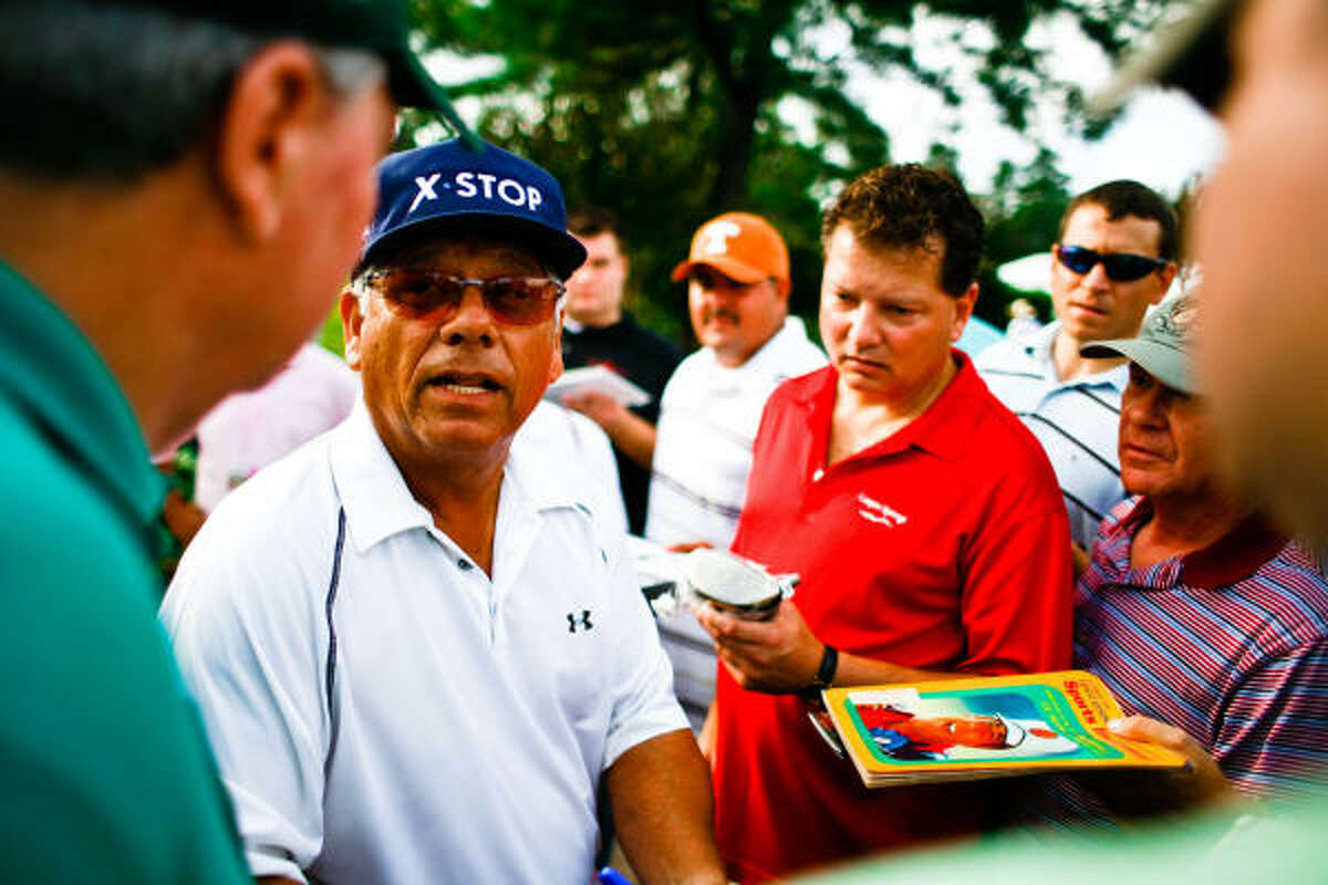 Lee Trevino gives autographs and talks to the crowd before teeing off.