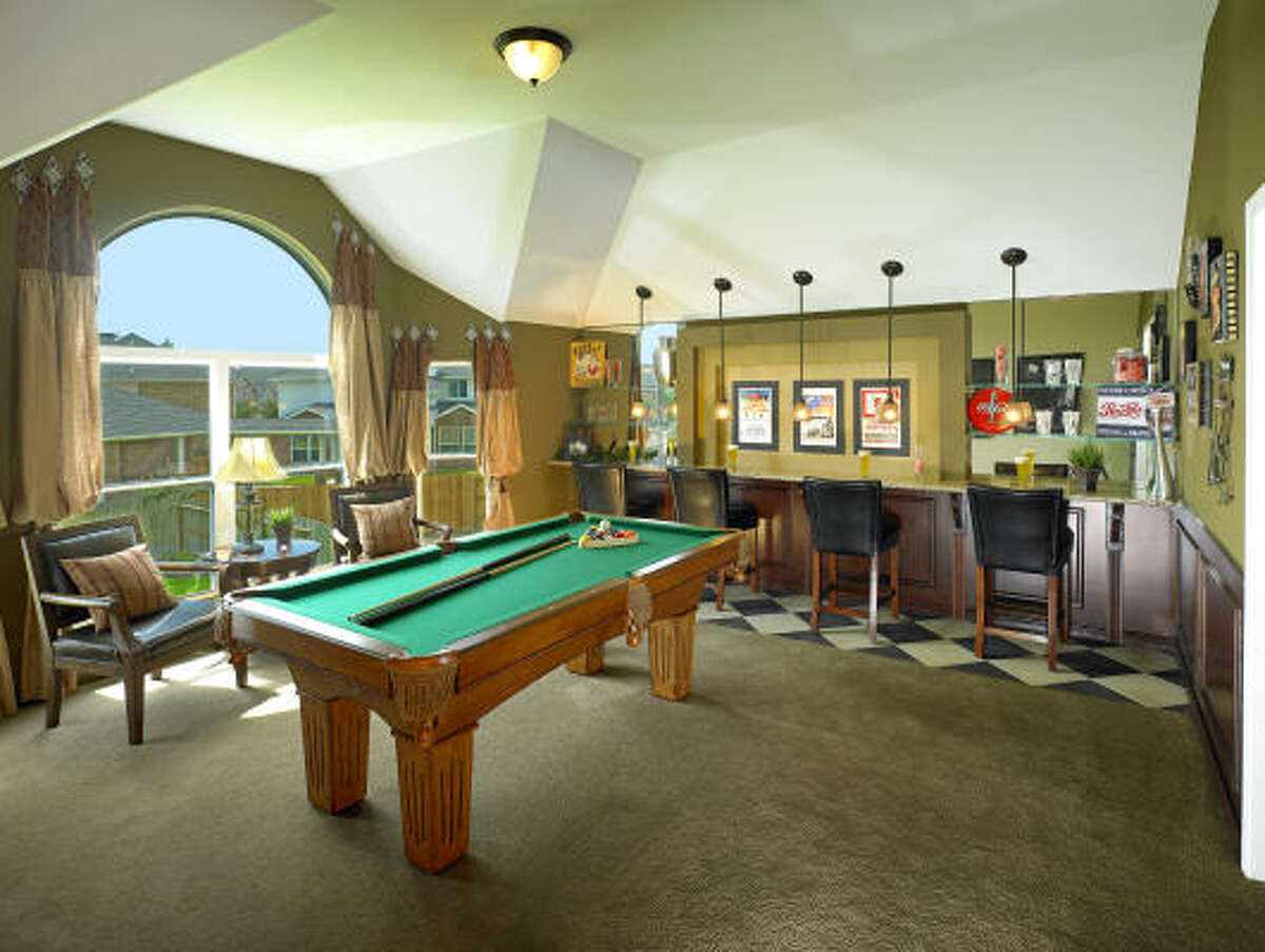 This classically designed game room has it all -- a pool table and a bar area for seating and drinks.