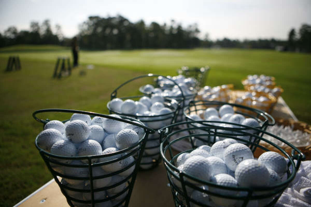 Golf balls wait for Administaff Small Business Classic competitors to practice before rain reaches The Woodlands Country Club.