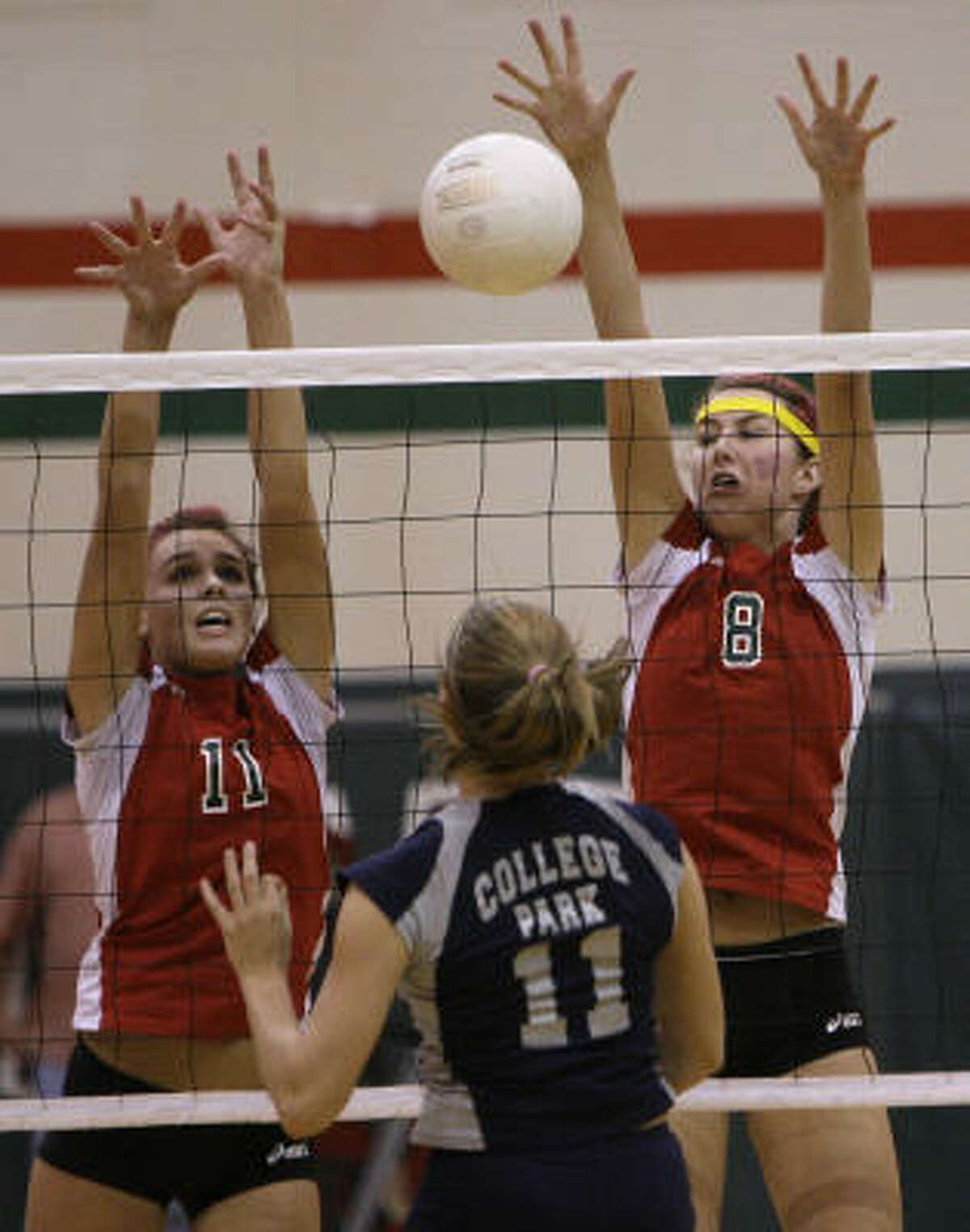 The Woodlands's Sarah Sanchez, left, and Katie Messing go up to block a shot by Abby Mayer.