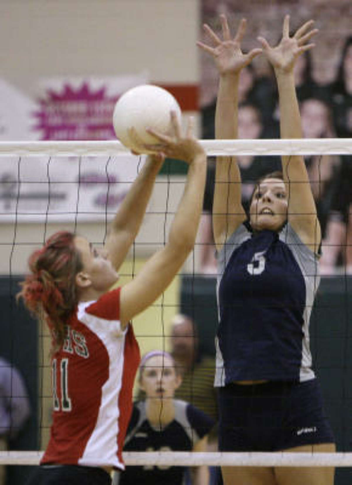 The Woodlands's Sarah Sanchez looks to set the ball as College Park Lauren Chapman goes up to block.