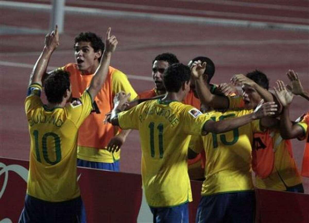 Los jugadores de Brasil, desde la izquierda, Giuliano, Paulo Henrique y Wellington Junior festejan tras un gol de Brasil contra Costa Rica en las semifinales del mundial sub20 el martes, 13 de octubre de 2009, en El Cairo.