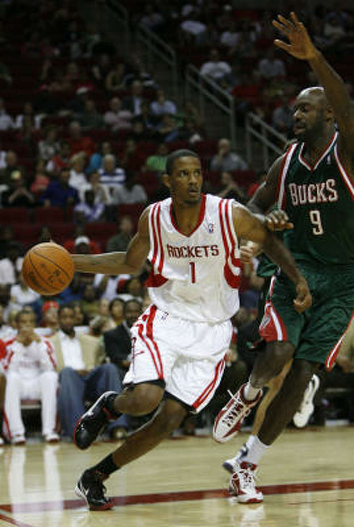 Rockets guard Trevor Ariza drives around Bucks' Francisco Elson during the first half.