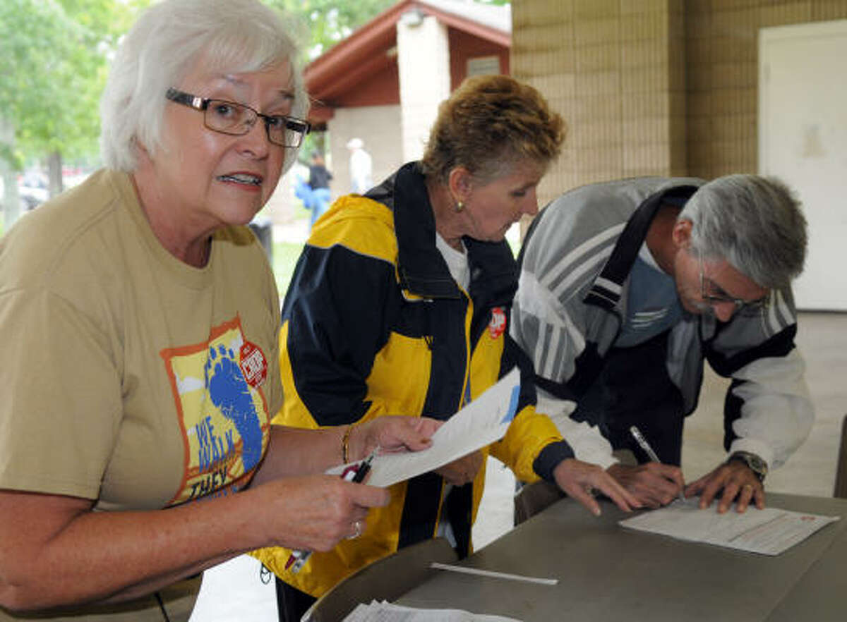 From left, Connie Nyquist, Pam Merrill and Robert Heselmeyer sign up for the walk.
