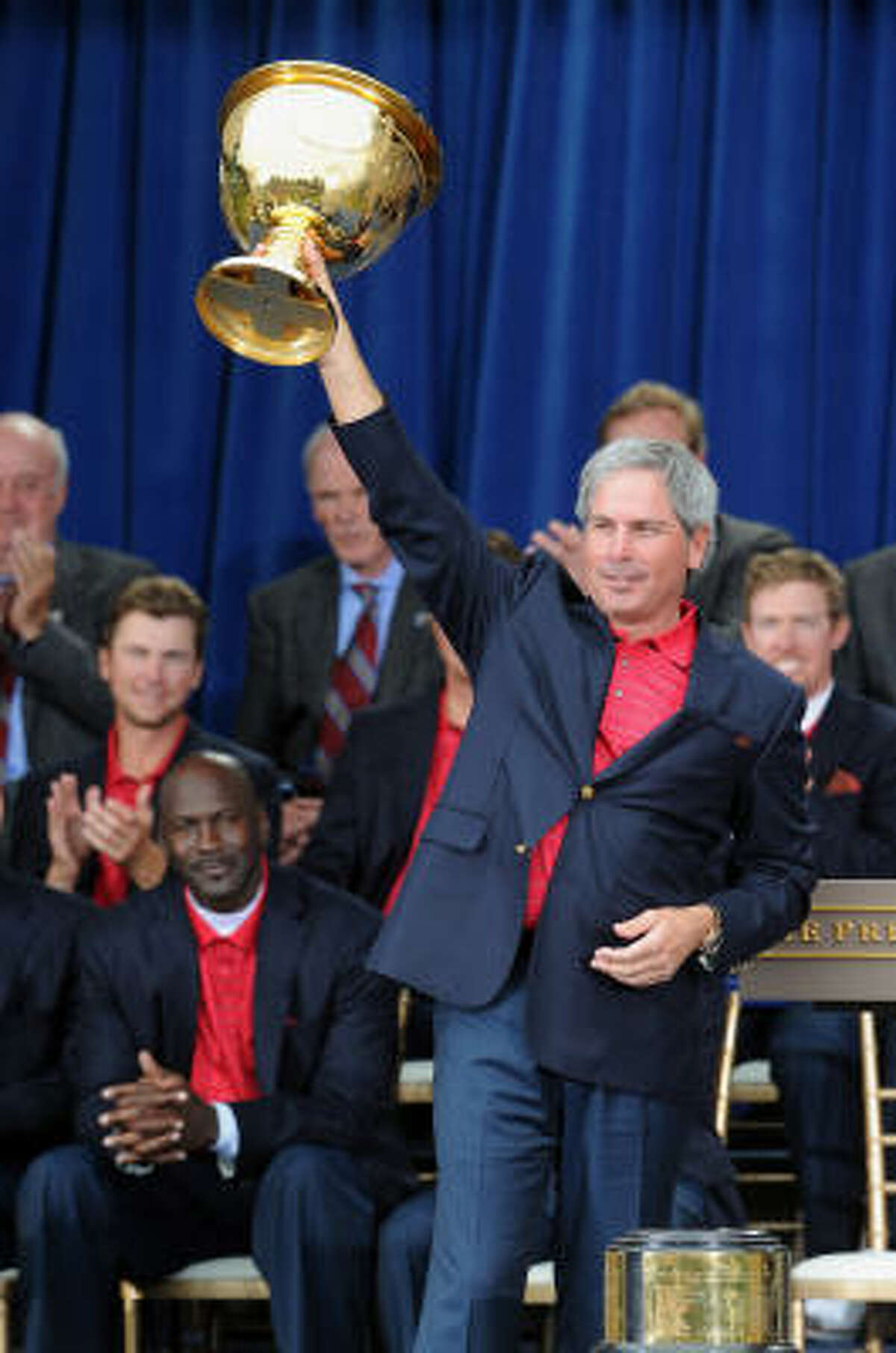 U.S. team captain Fred Couples raises the Presidents Cup trophy as the Americans celebrate their win on Sunday at Harding Park Golf Course in San Francisco.