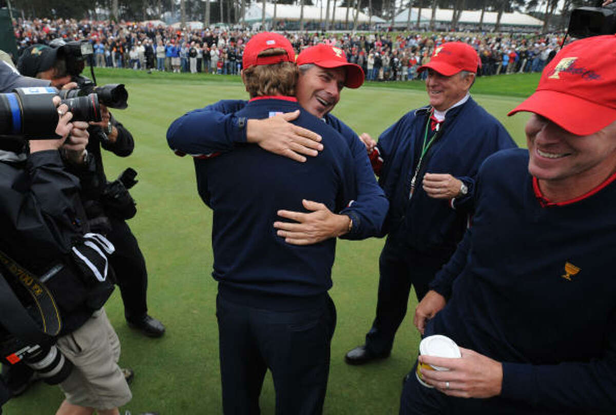 U.S. team captain Fred Couples hugs teammate Lucas Glover as they celebrate their win on the 18th green during the final round of the Presidents Cup.