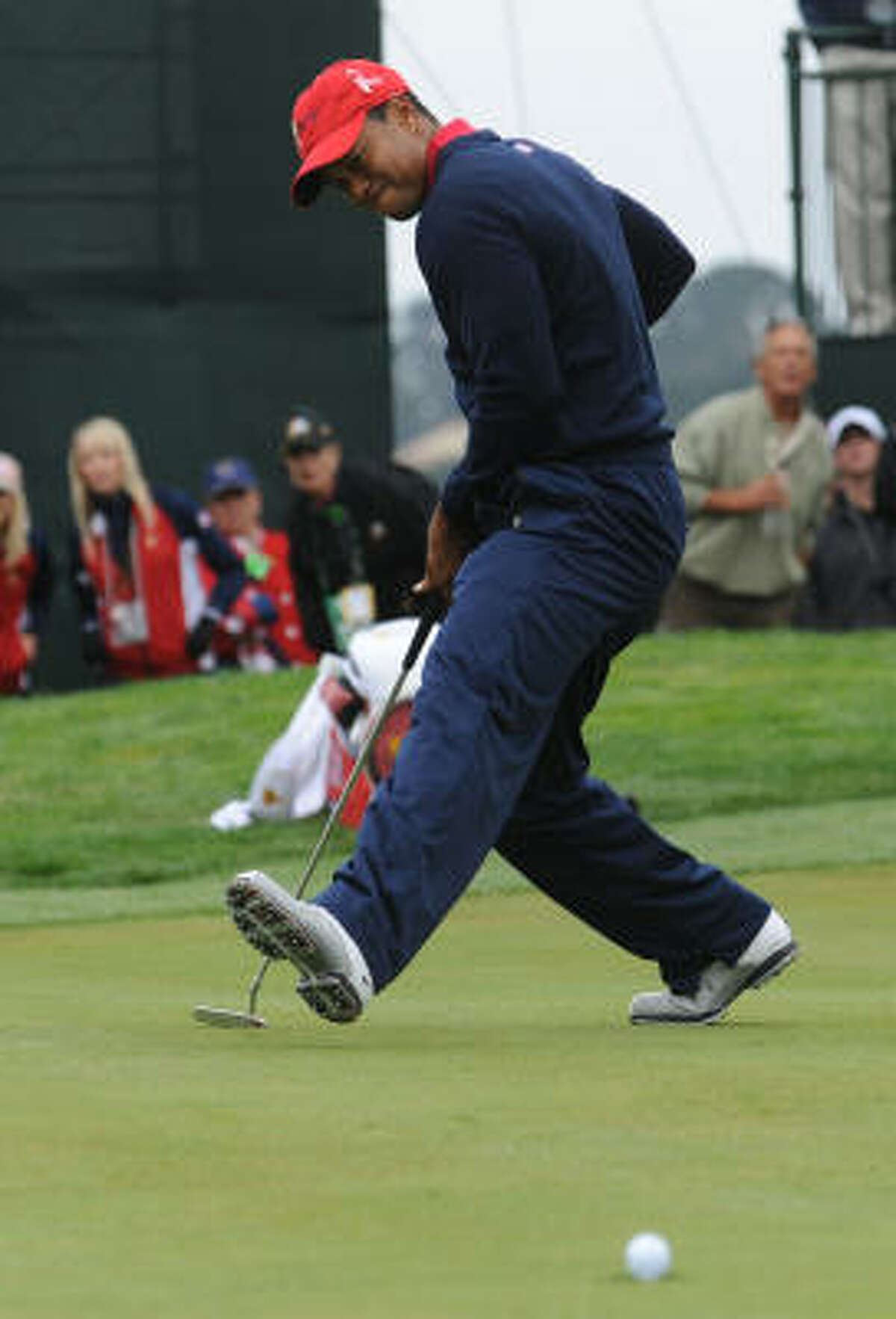 U.S. team member Tiger Woods prepares to celebrate as he sinks a putt on the ninth hole during the final round. He won all five of his matches, becoming only the third player in the Presidents Cup to do so.