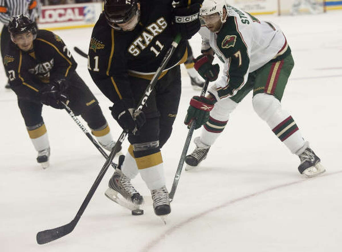 Aeros defender Clayton Stoner (7) steals the puck from Stars center Aaron Gagnon (11) in the first period.