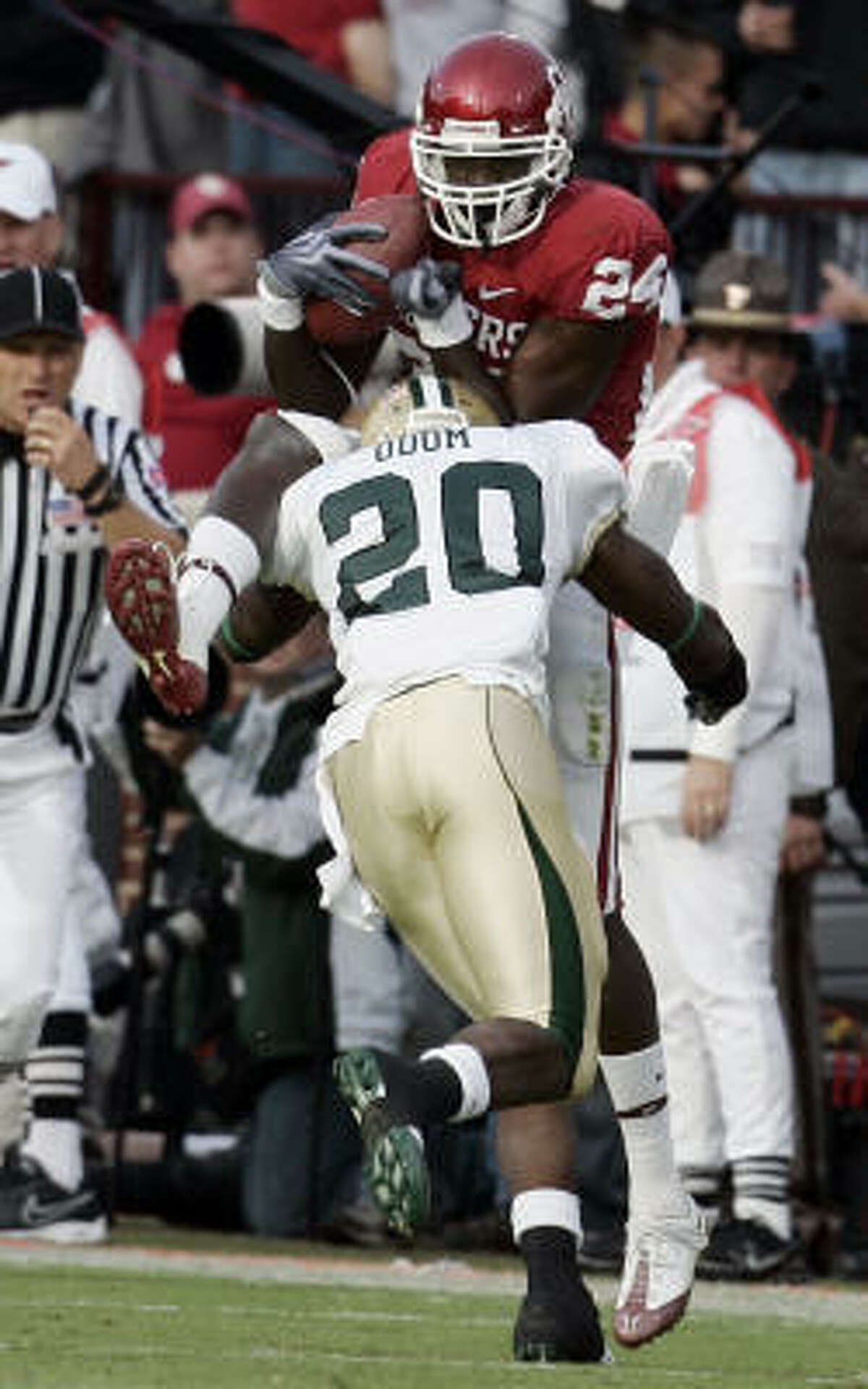 Baylor's Clifton Odom hits Oklahoma receiver Dejuan Miller, knocking the ball out of his hands and causing an incomplete pass in the fourth quarter in Norman, Okla.