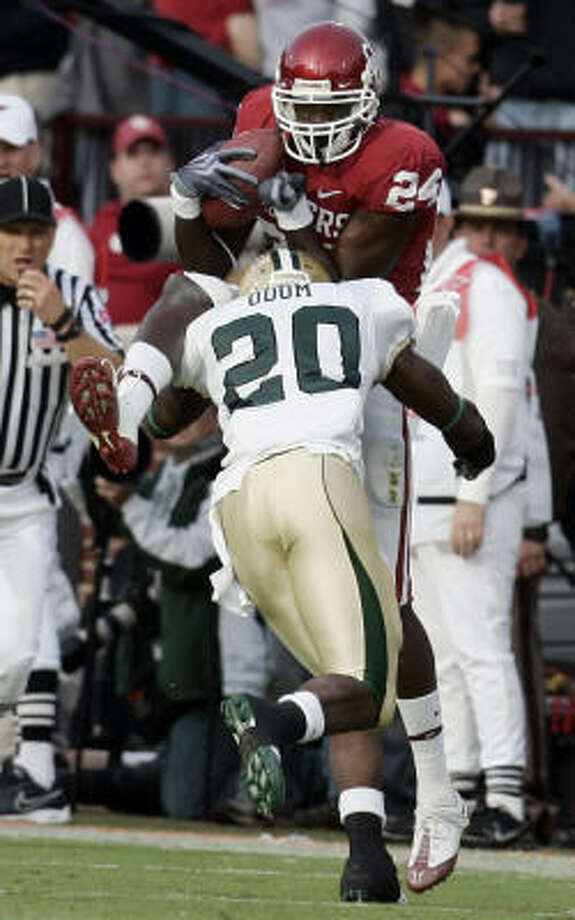 Baylor's Clifton Odom hits Oklahoma receiver Dejuan Miller, knocking the ball out of his hands and causing an incomplete pass in the fourth quarter in Norman, Okla. Photo: Sue Ogrocki, Associated Press