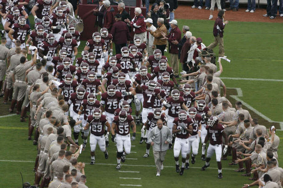 Billy Pickard, center, leads the Texas A&M football team onto the field prior to kickoff. Photo: Julio Cortez, Chronicle