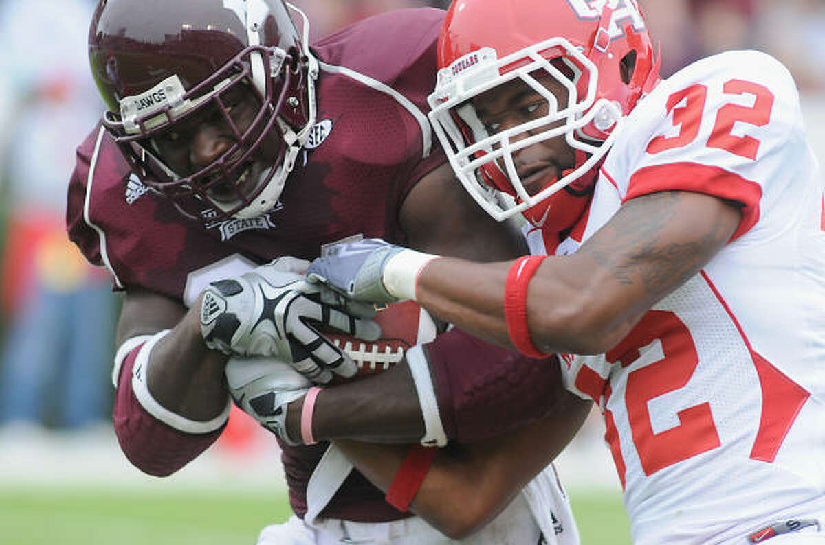 Mississippi State's Anthony Dixon, left, carries Houston's Jamal Robinson over the goal line.