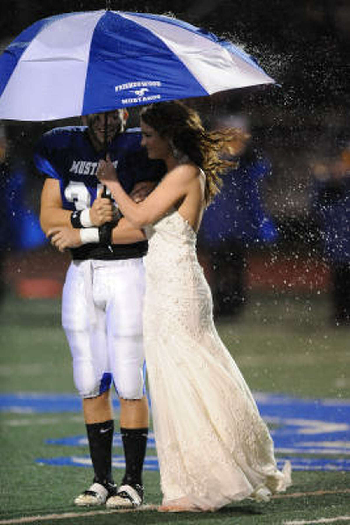 Queen candidate McKenna Harclerode and her escort, Sam Giamfortone, try to fend off the rain.