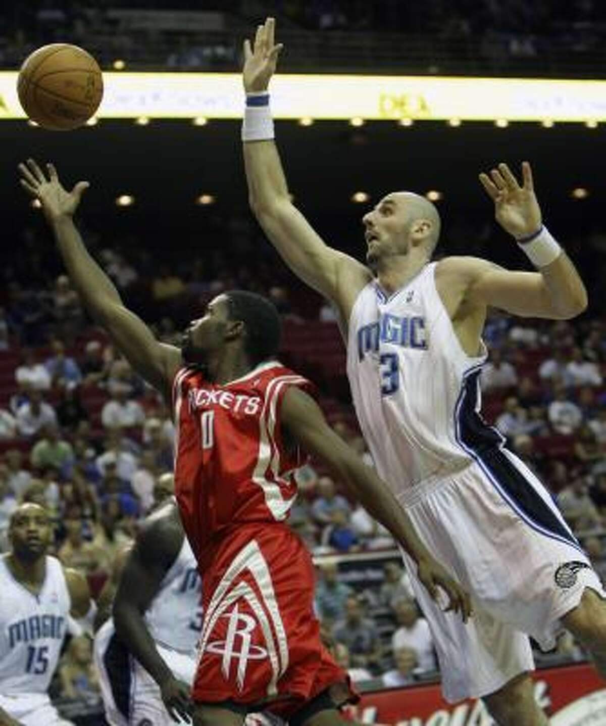 Rockets guard Aaron Brooks (0) goes up for a shot as Magic center Marcin Gortat goes in to block during the first half.