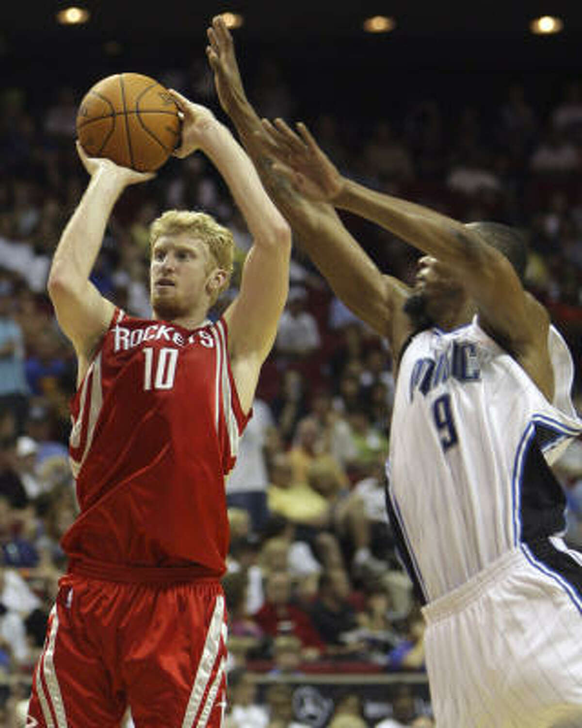 Rockets forward Chase Budinger (10) takes a shot over Magic forward Rashard Lewis during the first half.