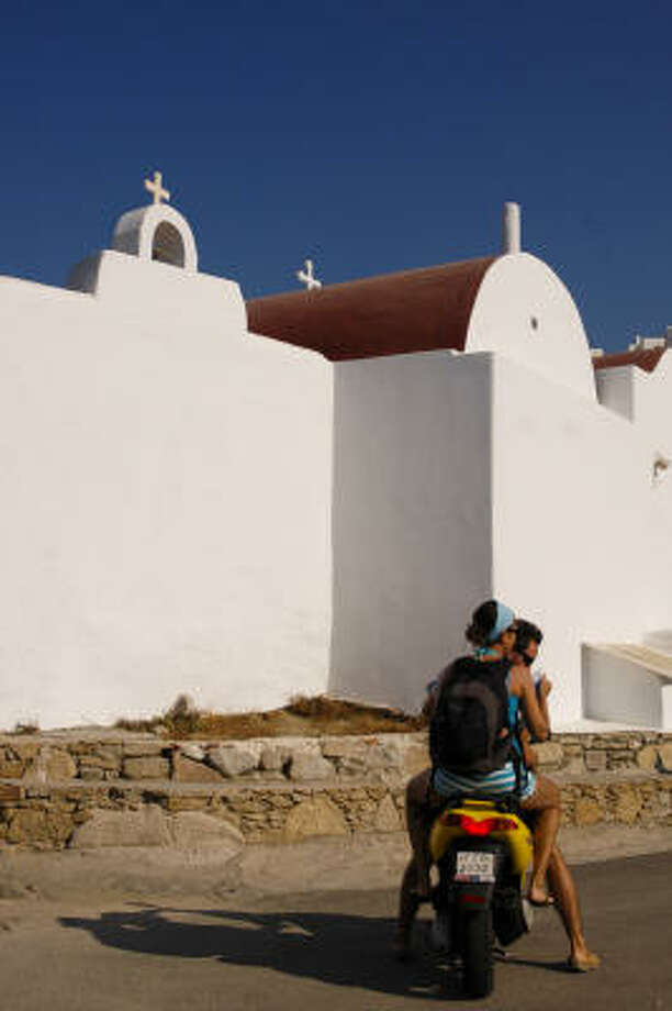 Motorcyclists pause beside a family church on Mykonos. Tourism lore is that the Greek island -- population 11,000 -- contains 365 churches, one for every day of the year. In reality, the number is between 400-500. Many are small family churches. Following tradition, all face west and are painted white. Photo: Joan Shattuck, For The Chronicle
