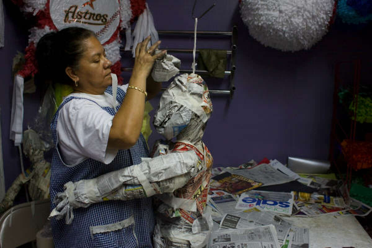 Rosa Martinez, who has been making pinatas for eight years at Fiestas y Creaciones Haeily on the 1000 block of Studewood in the Heights, gets a hug while building a Frankenstein pinata. Martinez said the average pinata takes two days to make and in a busy week they will make about 25. Martinez said she loves the reaction the children get when they see a pinata.