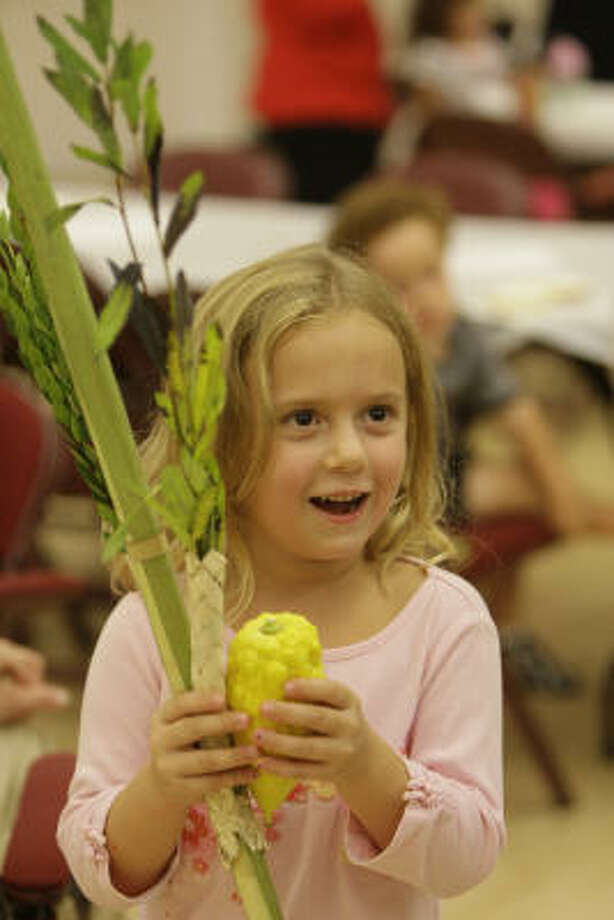 Riley Evans, 5, performs the shaking of the lulav during a Sukkot program for the Bertha Alyce Center preschoolers at the Jewish Community Center. It is made up branches of palm, mrytle and willow along with an etrog, a citrus fruit similar to a lemon native to Israela. The blessing and the shaking of the lulav and etrog, commonly symbolize the bringing together of all communities, said Jonathan Fass, co-director of the center for Jewish Living and Learning at the JCC. Photo: Melissa Phillip, Chronicle