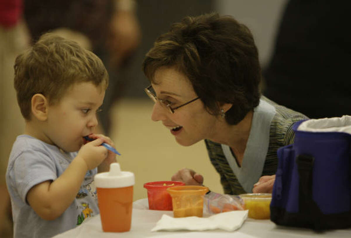 Janis Block with her grandson, Joshua Black, 2, during a Sukkot program for the Bertha Alyce Center preschoolers at the Jewish Community Center. Hot weather changed the plans to have the children eat in a sukkah, a temporary structure constructed for use during the week-long Jewish festival of Sukkot. They did place art work in the sukkah and had a cookie in the sukkah.