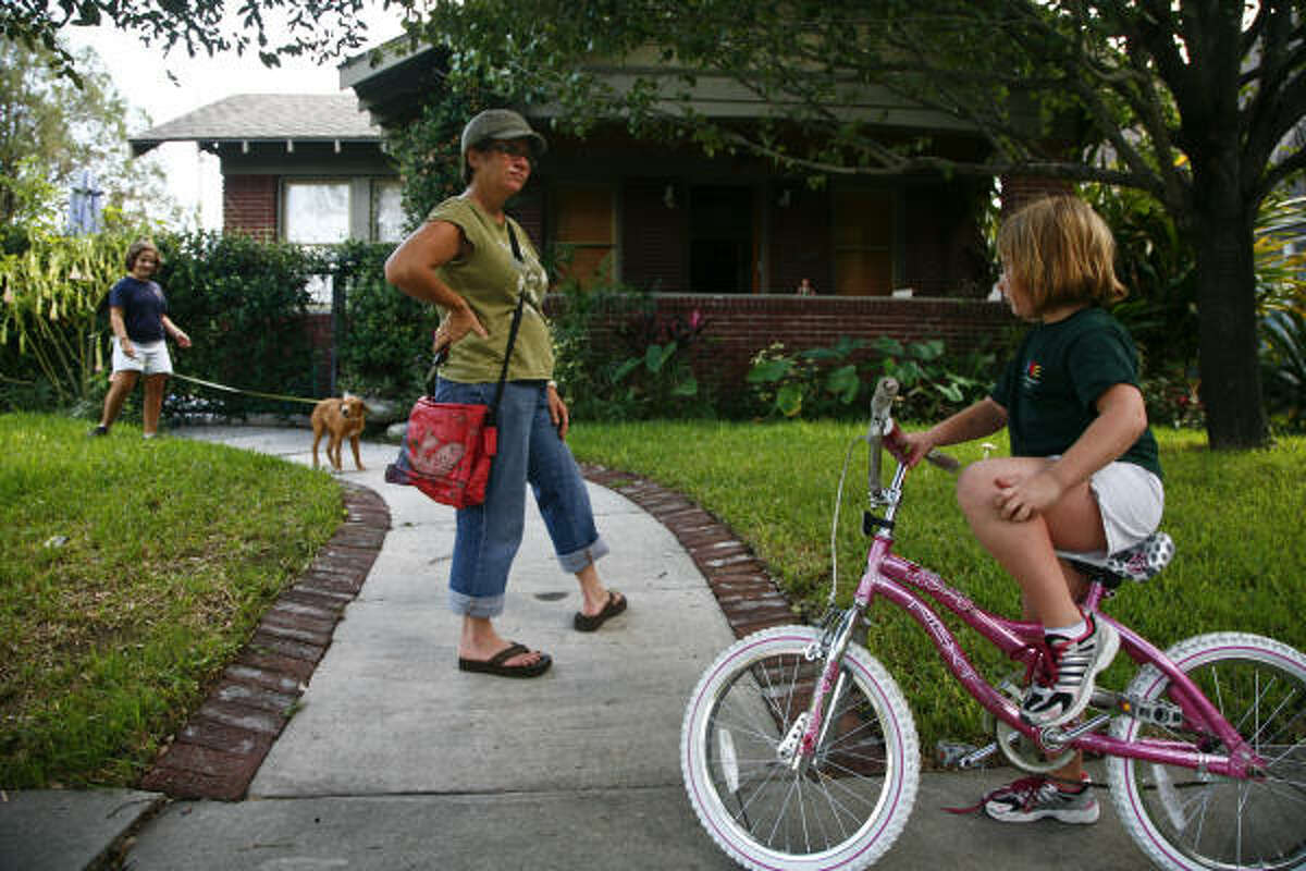 Blythe Fergus-Peterman, 6, rides her bike as her mom, Karen looks on and her sister Beryl, 10, walks the family dog, outside the family's home in the Montrose area.