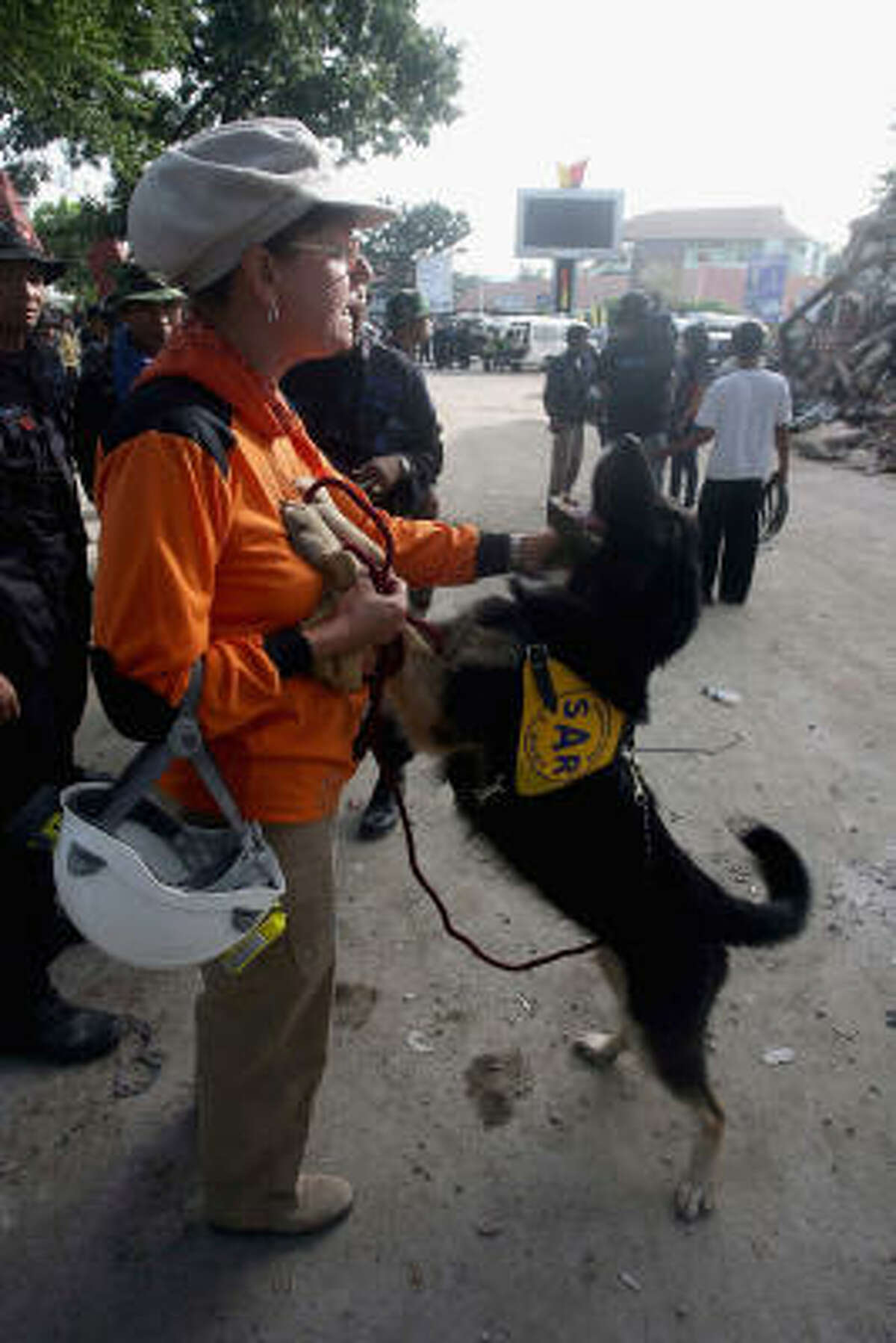 A German rescuer waits with her dog in preparation to assist at the collapsed Ambacang Hotel building site on Oct. 2 in Padang, West Sumatera, Indonesia.