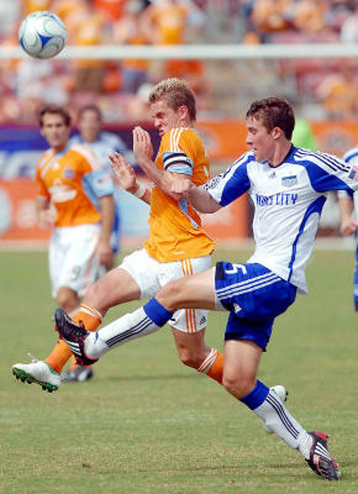 Houston's Stuart Holden (left) and Kansas City's Matt Besler battle for the ball.
