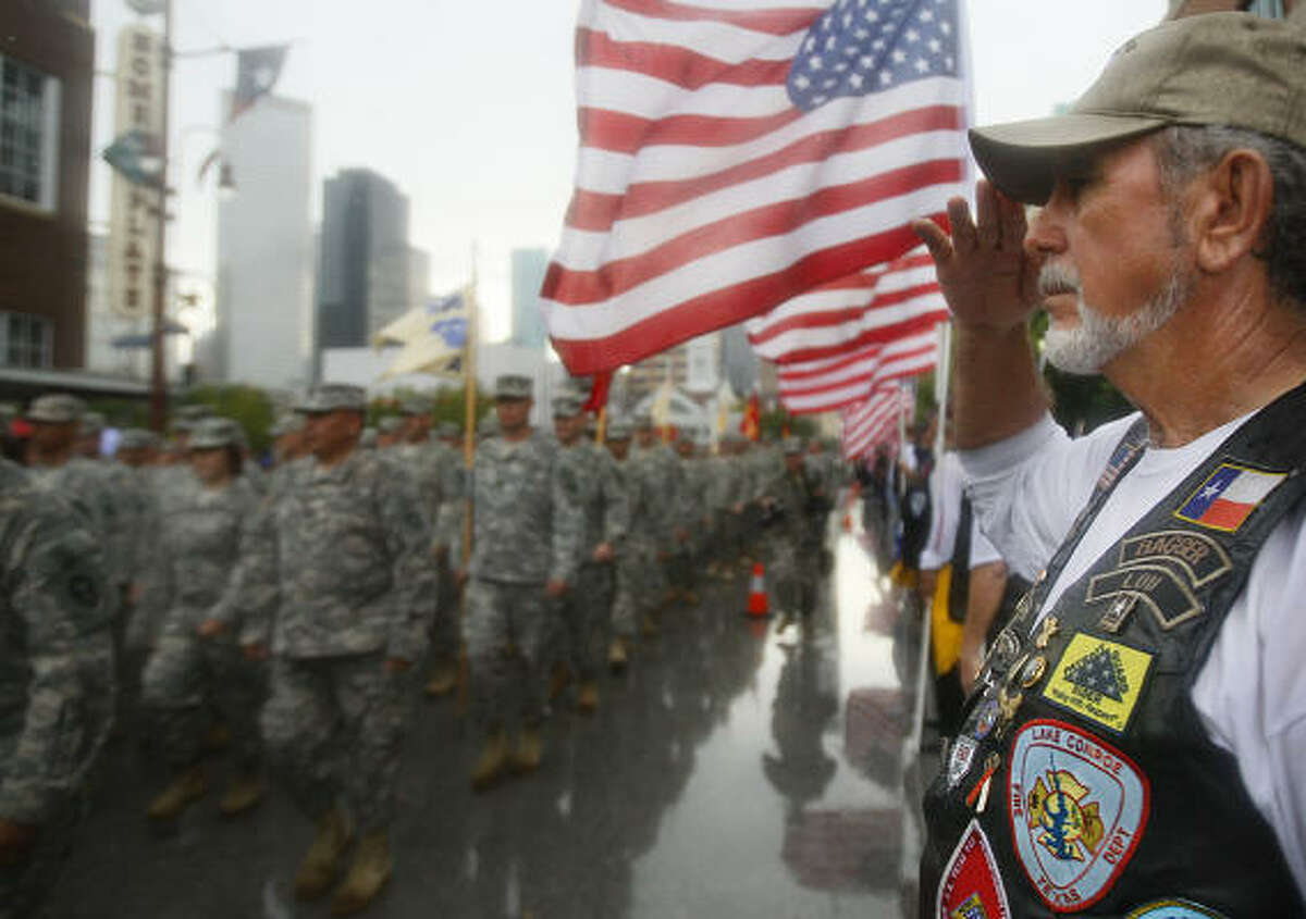 Lou Freitas salutes the 72nd Infantry Brigade Combat Team as it marches past on Texas Avenue.