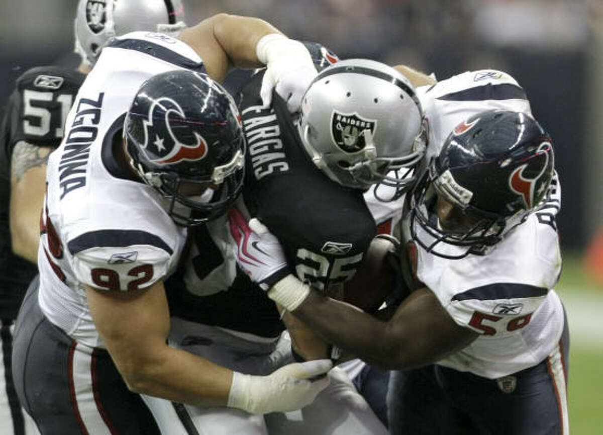Texans defensive tackle Jeff Zgonina (92) and linebacker DeMeco Ryans (59) stop Raiders running back Justin Fargas for no gain.