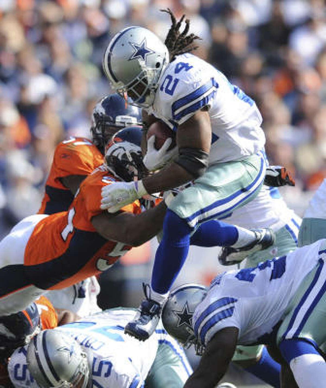 Broncos linebacker Andra Davis (left) dives to tackle Cowboys running back Marion Barber (24) during the second quarter.