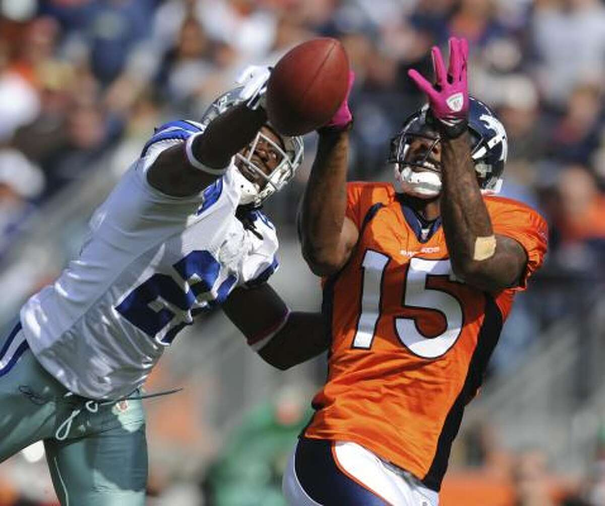 Cowboys cornerback Mike Jenkins (left) breaks up a pass intended for Broncos wide receiver Brandon Marshall during the second quarter.