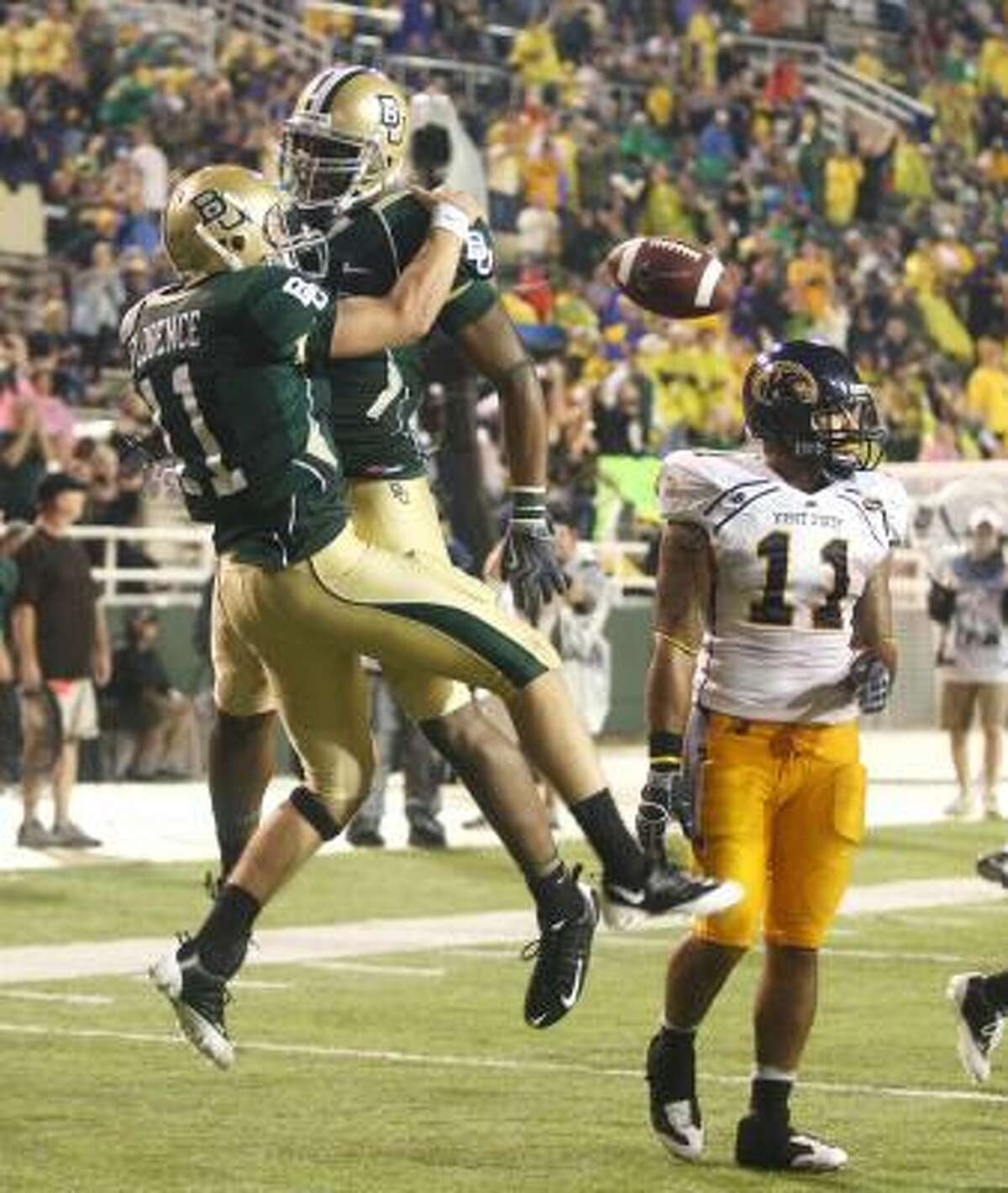 Baylor quarterback Nick Florence, left, celebrates his third-quarter touchdown with teammate Brad Taylor in front of Kent State defender Cobrani Mixon, right.