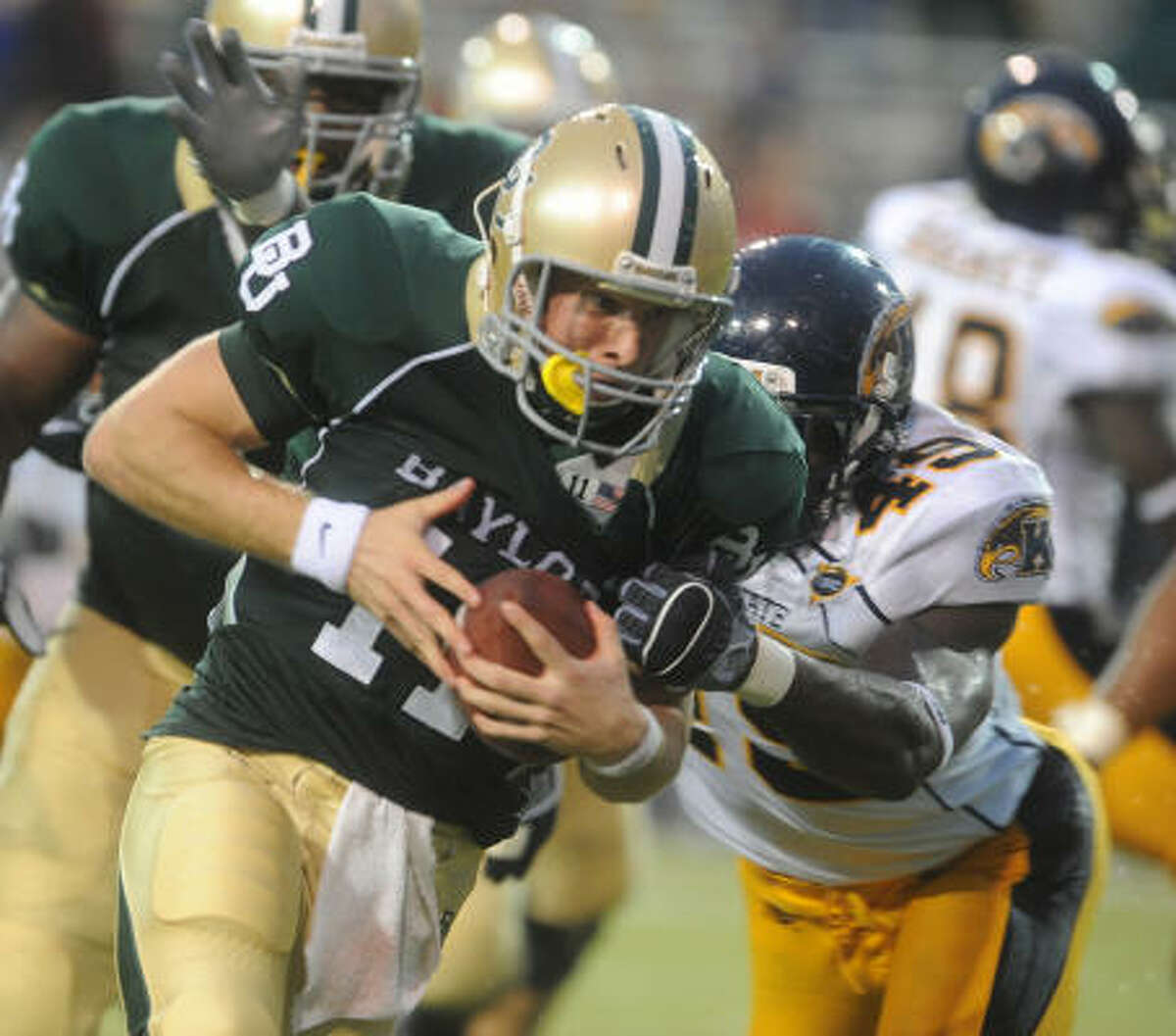 Baylor's Nick Florence, front, eludes Kent State defender Monte Simmons (49) on a second-quarter touchdown run.