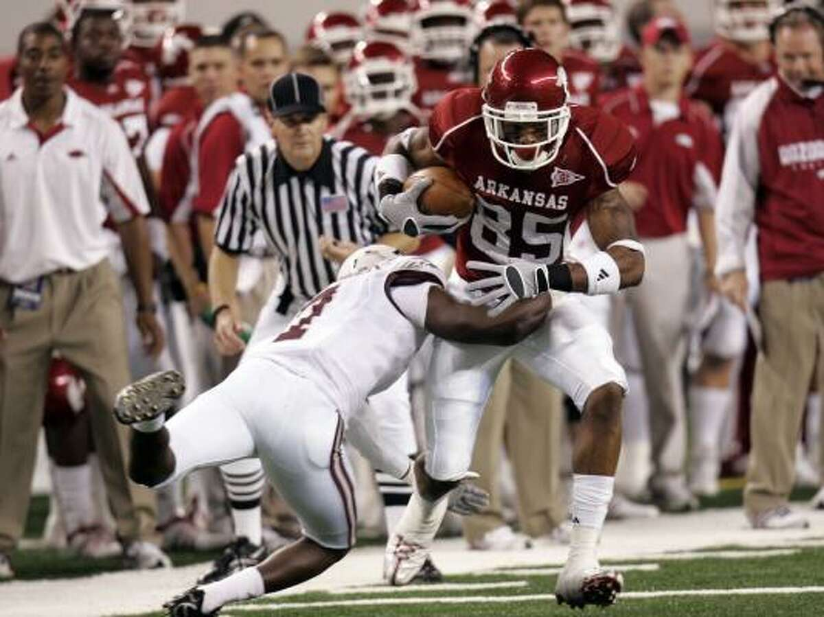 Arkansas' Greg Childs runs for yardage after a catch against Texas A&M's Terrence Frederick.