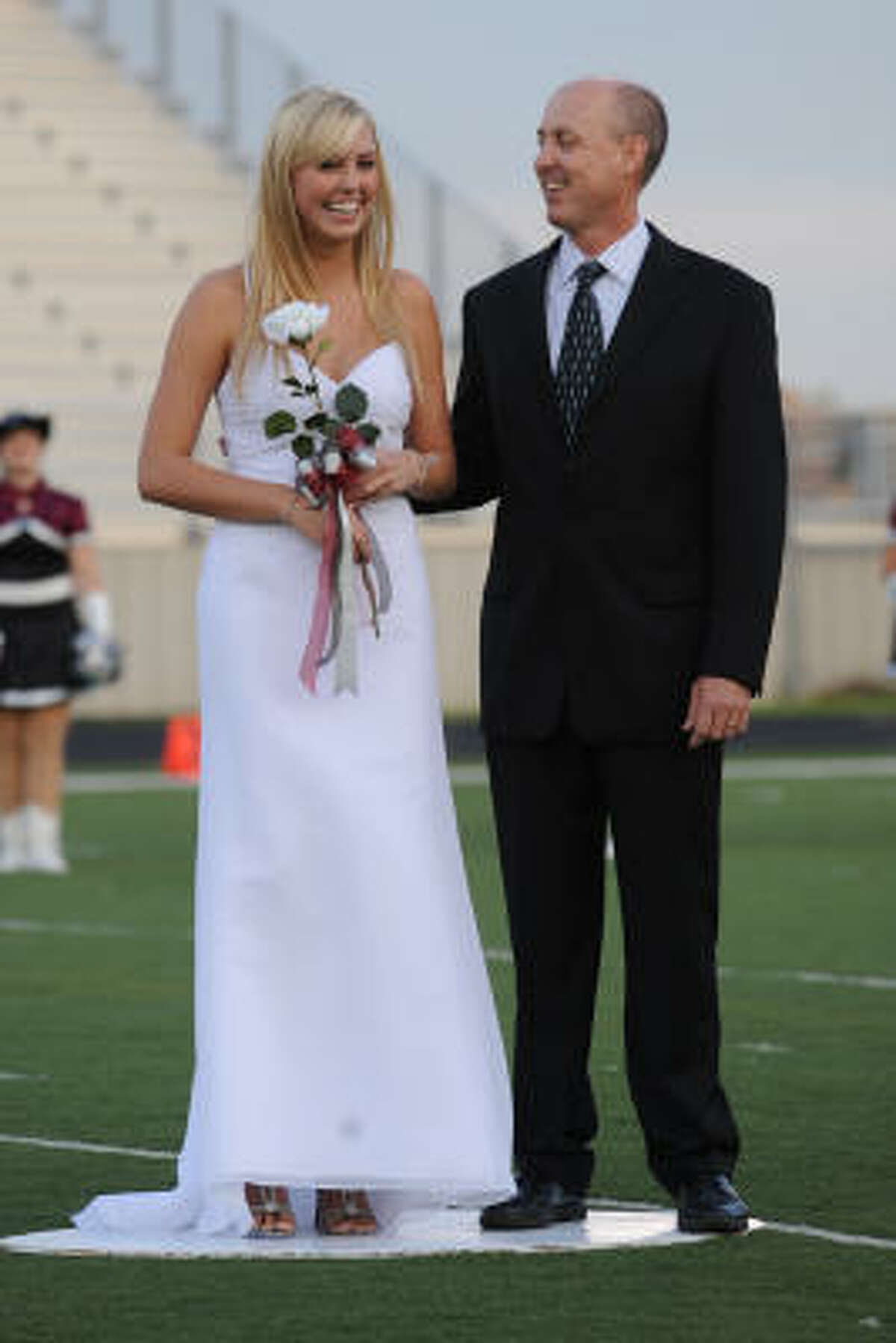 Katelyn Knight and her dad, John Knight, react to Katelyn being named Pearland's Homecoming Queen during a pre-game ceremony at The Rig stadium.