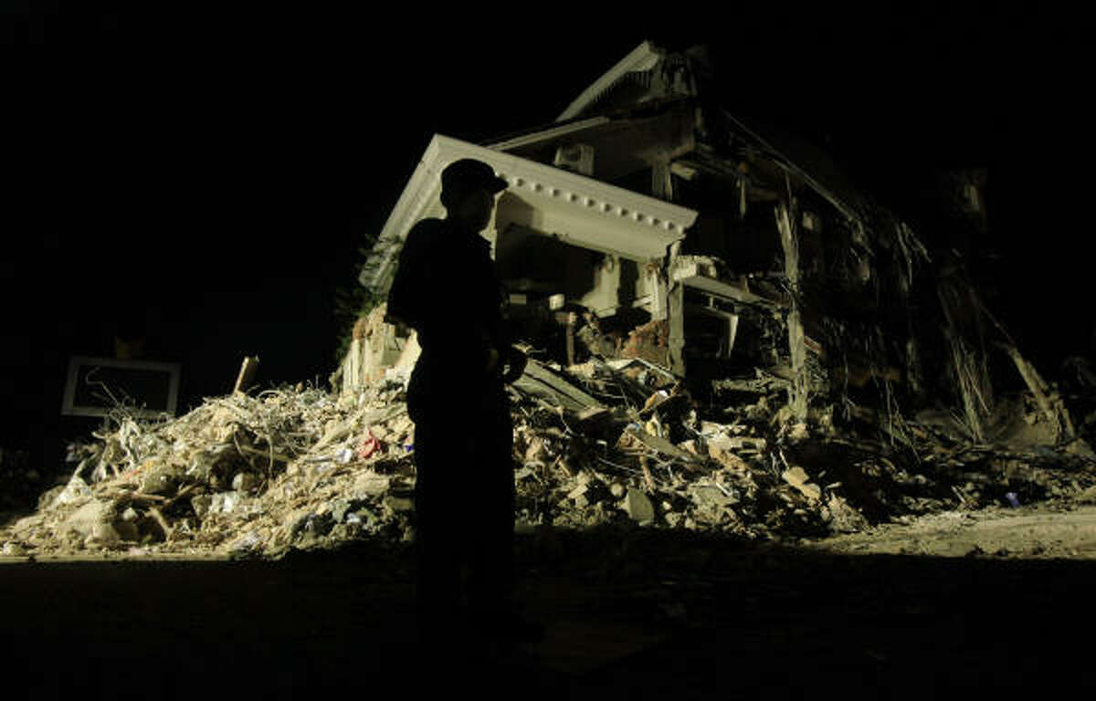 A police officer is silhouetted against the Ambacang Hotel, which was badly affected by the earthquake.