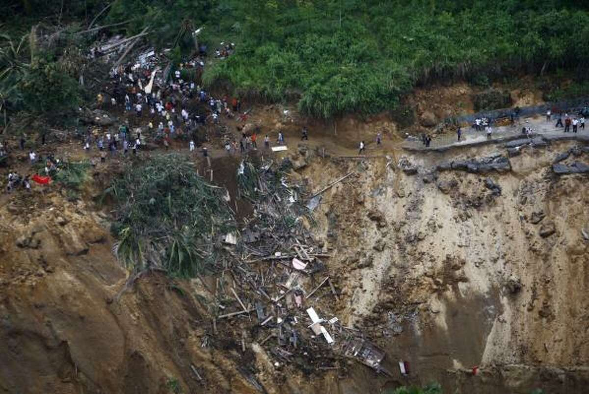 People survey the damage in this aerial photo of an area affected by an earthquake-triggered landslide in Padang Pariaman, West Sumatra, Indonesia.