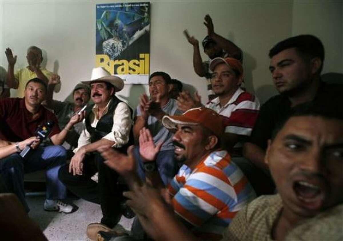 El presidente hondureño derrocado Manuel Zelaya, con sombrero, habla con los reporteros mientras sus partidarios celebran dentro de la embajada brasileña en Tegucigalpa el miércoles 23 de septiembre del 2009