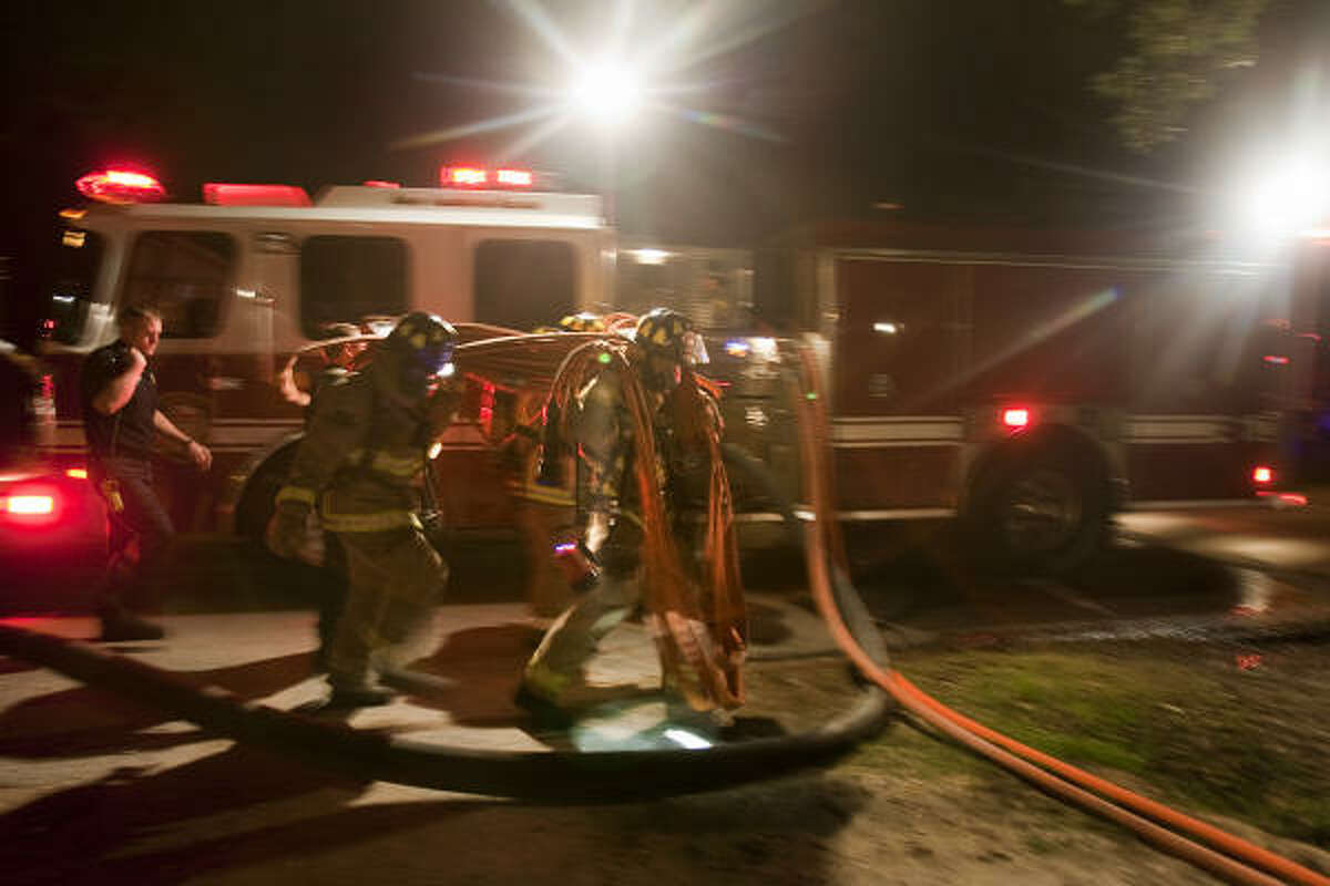 Firefighters rush to set hoses to fight a fire suspected to be the latest in a string of over a dozen suspicious fires in the Heights area.