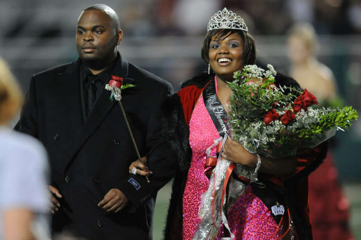 Ta-Mickey Brooks is escorted off the field at Veterans Memorial Stadium by her brother Gary Hall after being named Clear Brook's Homecoming Queen.