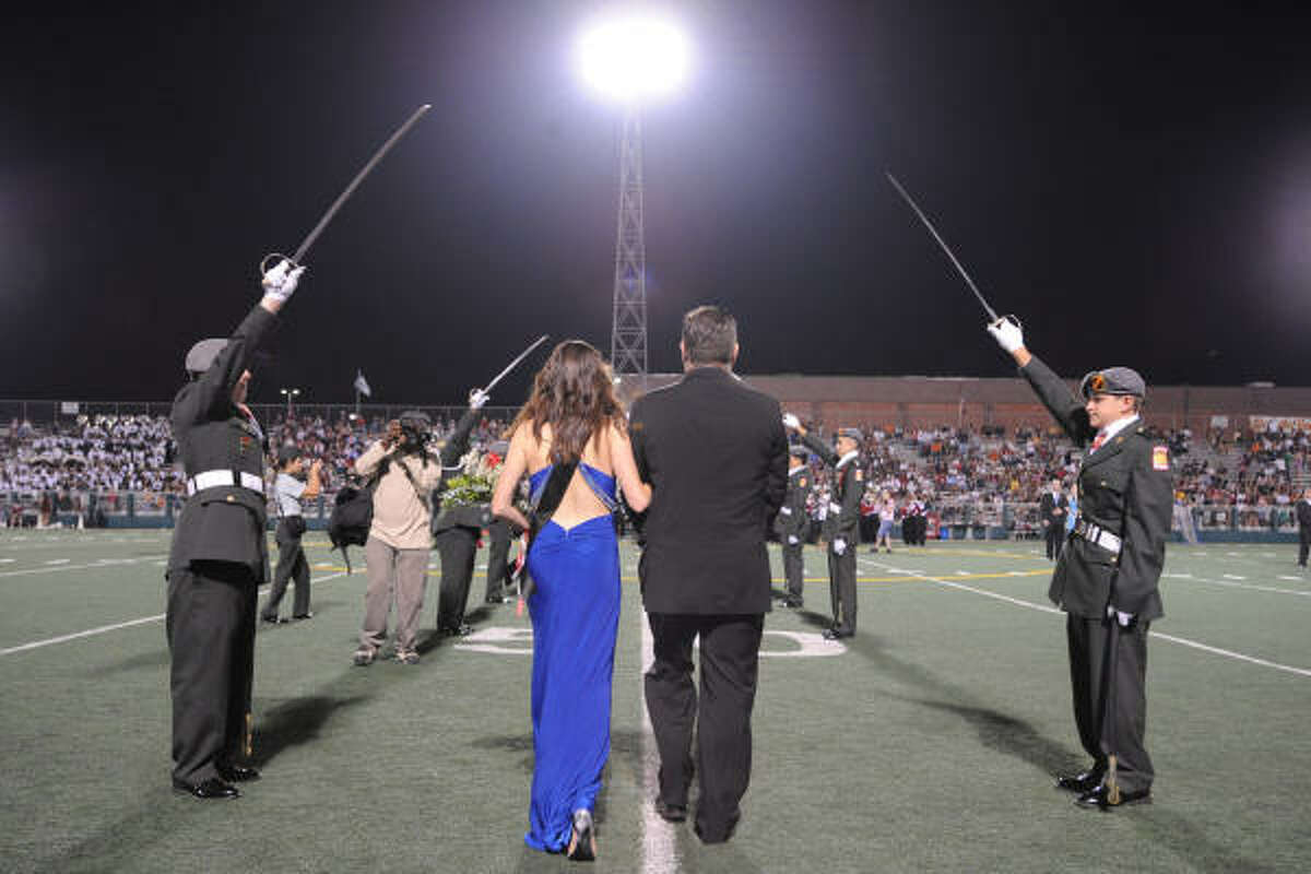 Elliott Marsh is escorted onto the field at Veterans Memorial Stadium by her dad Matthew Marsh during Clear Brook's homecoming queen ceremony.
